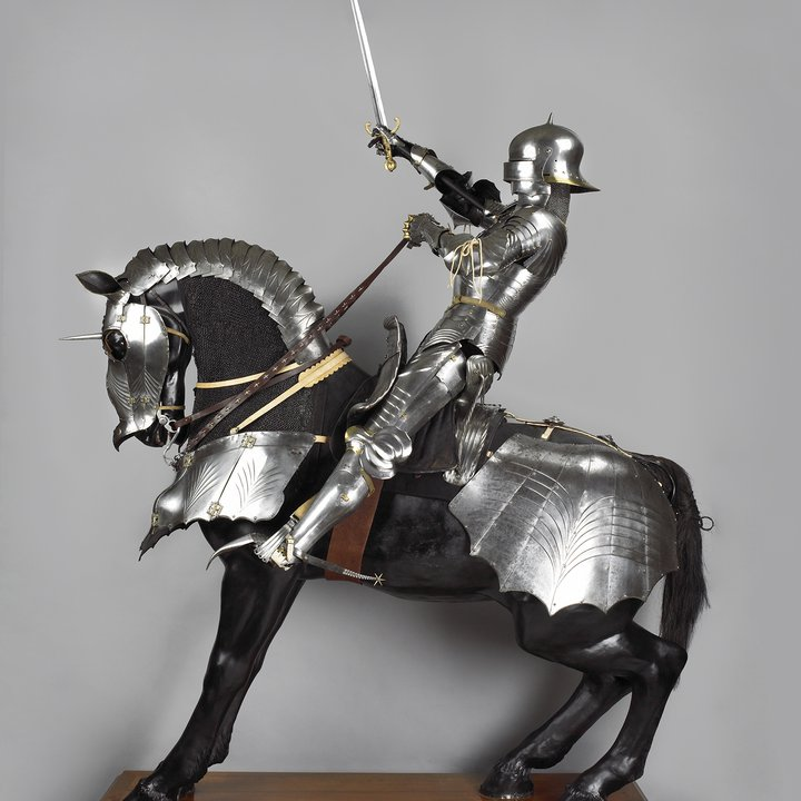Full length photograph of a medieval knight on an armoured horse from the left