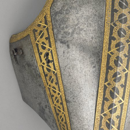 Close up of sixteenth century breast plate with visor with gold detailing