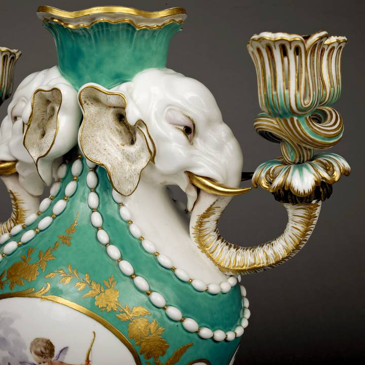 Side view detail of green and white vase with two elephant heads
