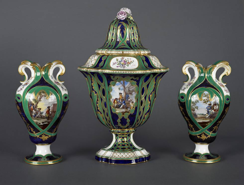 Three vases of blue and green with an rural setting illustration, centre vase has lid