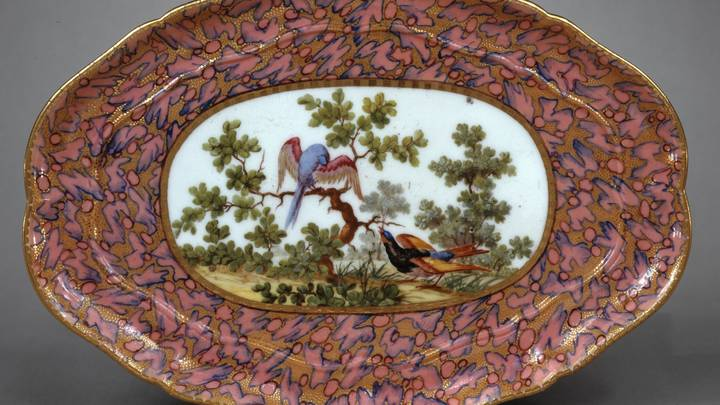 Plate from a tea service with pink and gold surrounding an image of birds in a tree
