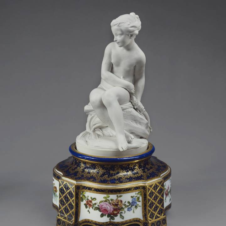 Porcelain sculpture of young women on floral painted pedestal