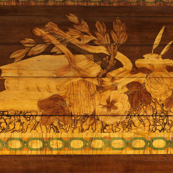 A detail of pictorial marquetry on the tambour of a roll-top desk