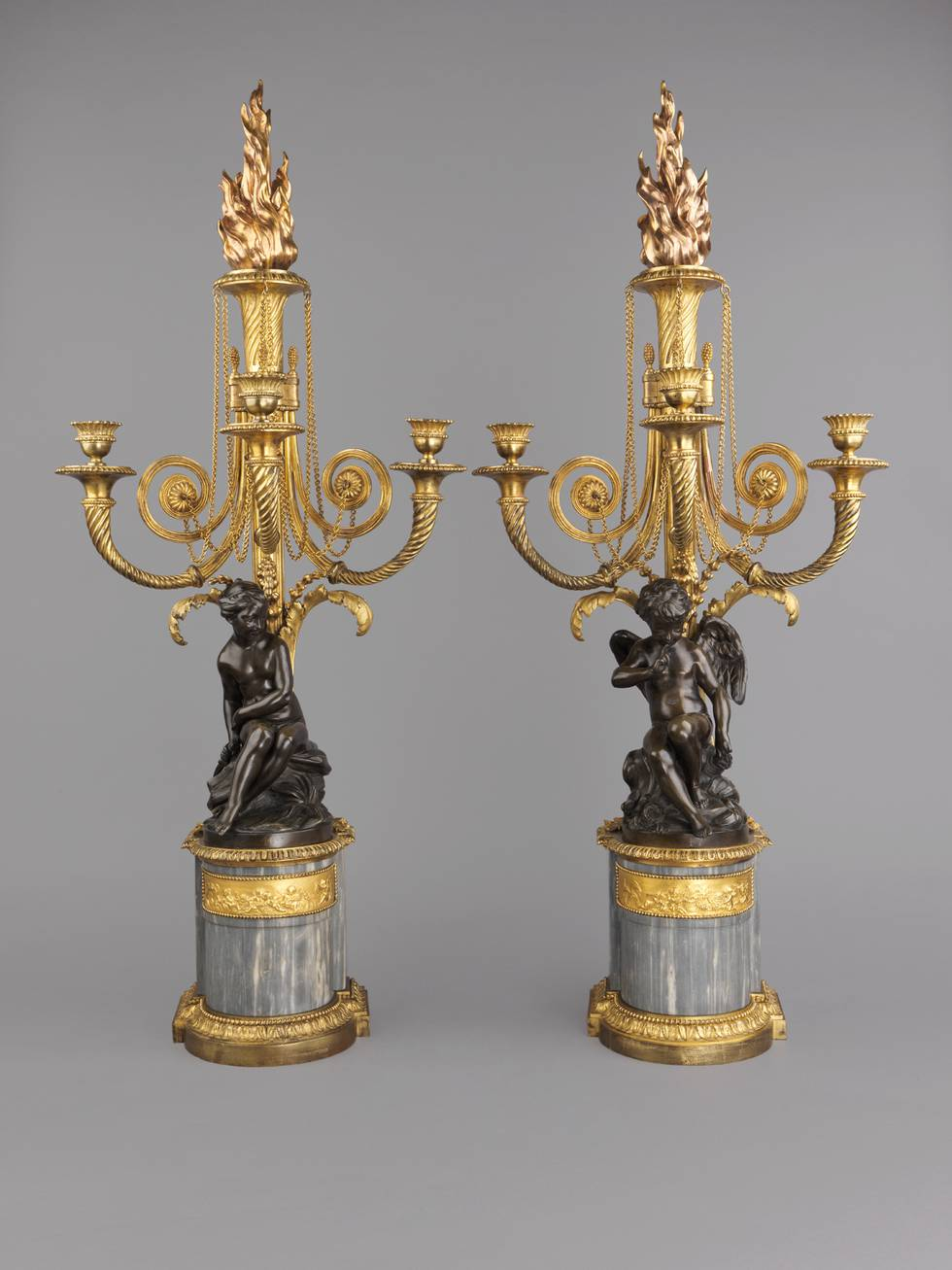 Pair of gold candelabrums, a figure at base