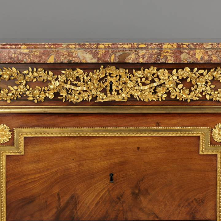 A detail of the gilt-bronze frieze mounts of a mahogany-veneered chest of drawers