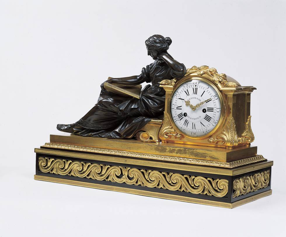 Statue of women sitting and leaning against a clock face