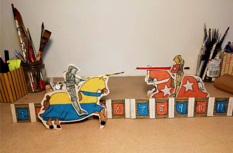 Two paper jousting horses on a desk