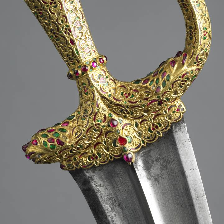 Detail of gold jewelled dagger handle with lion head