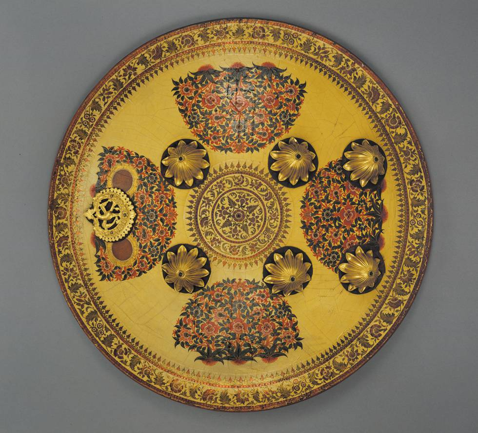 Round yellow shield with floral illustrations and gilt metal bosses
