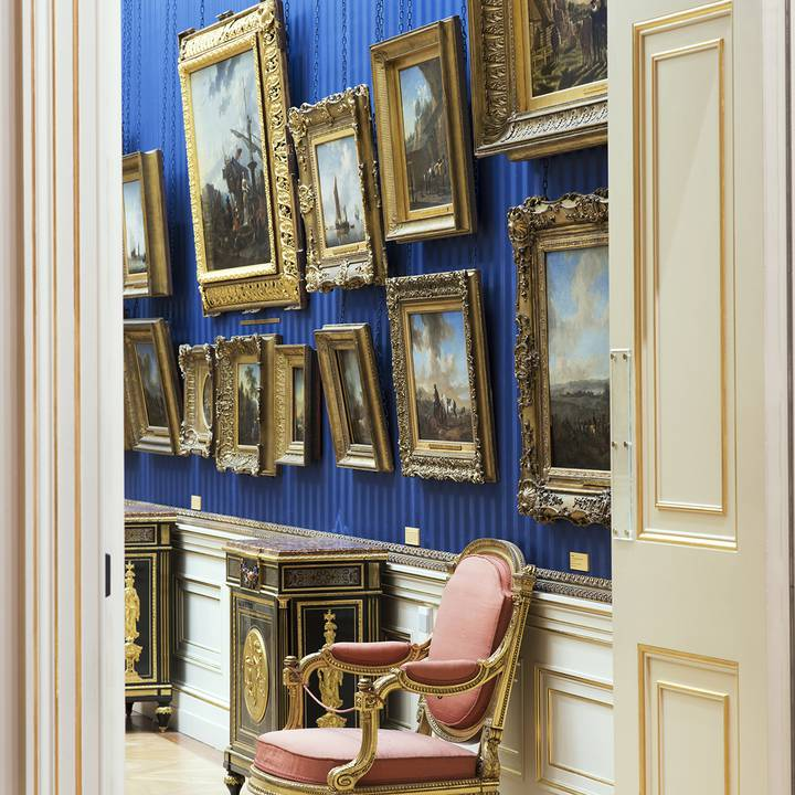 View through a door frame of paintings on gallery wall