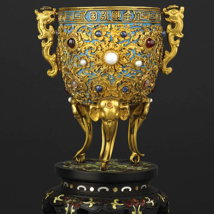 Gold cup decorated with jewels and blue bird feathers on stands